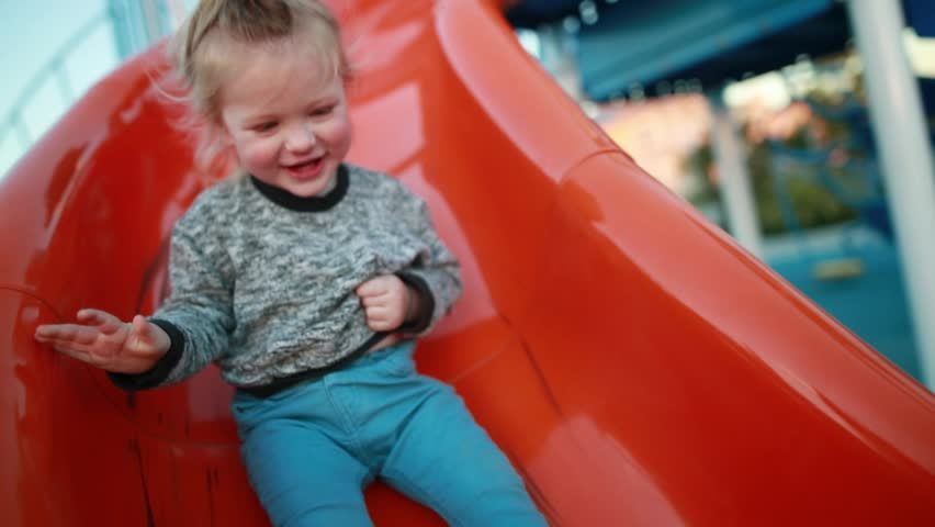A young toddler laughs and enjoys the playground at a park as he slides down the slide. #1024707092