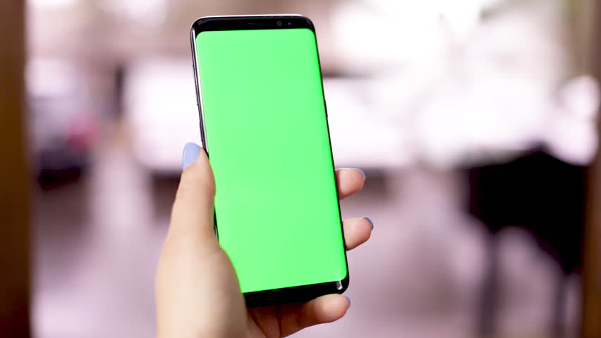 Women hands holding smart phone with green screen. Women using mobile phone while standing near window. Over shoulder shot. Chroma key | Shutterstock HD Video #1024711538
