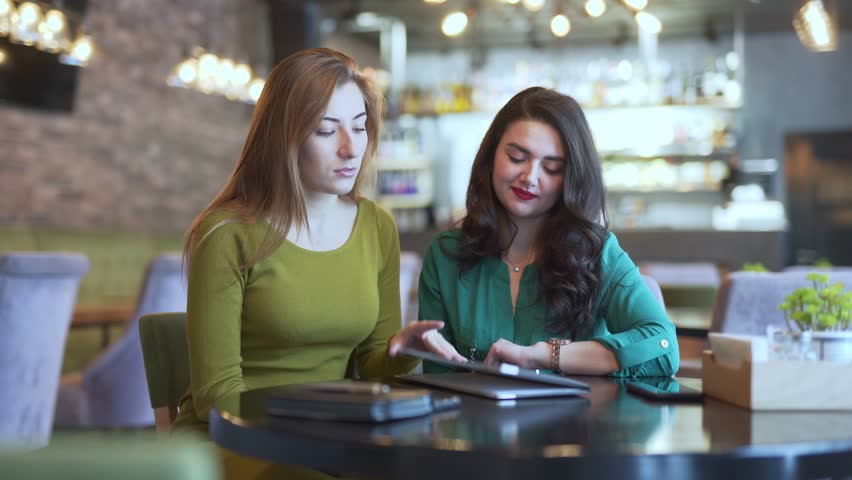 Two girls are at the café. They are sitting at the table and choosing what to order in the menu. #1024713509