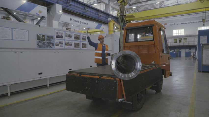 S-Petersburg, Russia, Seprt. 2018 - Factory worker in a hard hat is moving a metal detail with a remote crane | Shutterstock HD Video #1024727441