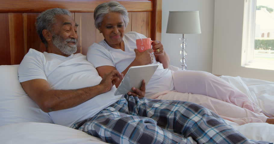 Mature African american couple making video call on digital tablet at home. Social distancing and self isolation in quarantine lockdown for Coronavirus Covid19