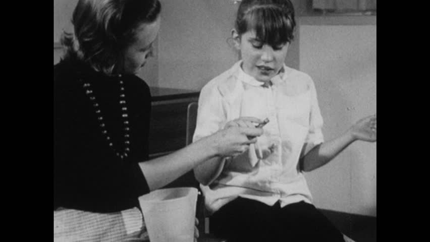 1960s: Woman hands girl crayon and asks what color it is. Girl fidgets and flails her hands.
