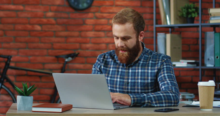 Portrait shot of the Caucasian young man with red beard working and tapping on the laptop computer in the office room and then smiling to the camera while showing gesture ok. | Shutterstock HD Video #1024755386