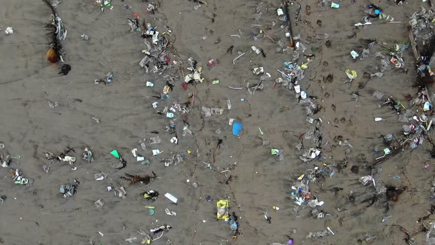 Pulling back aerial shot of an ecological disaster, plastic waste on the beach dying planet   Shutterstock HD Video #1024759376