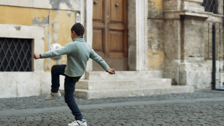 Active boy kicking a soccer ball and playing happily in a quiet street outside a buildings. Wide shot on 8k helium RED camera.