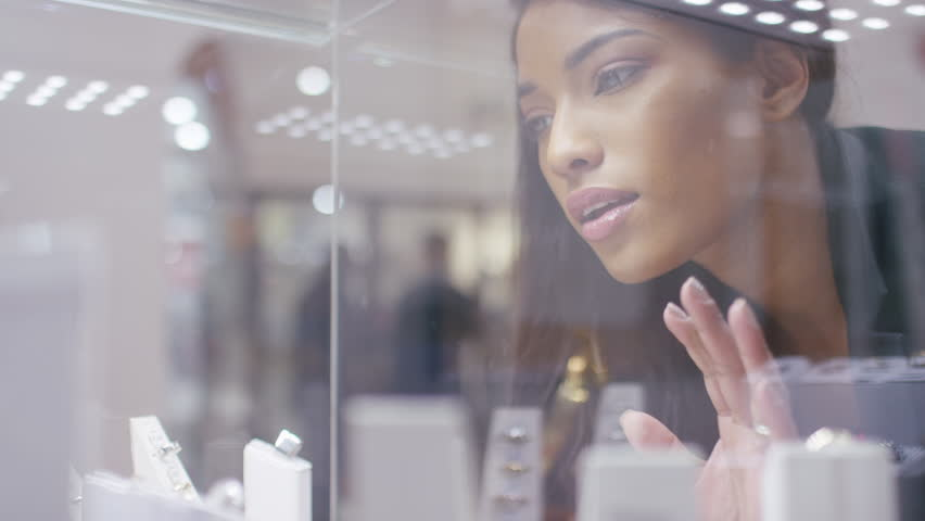 Young female seen looking at jewellery in a store, shot through glass | Shutterstock HD Video #1024766861