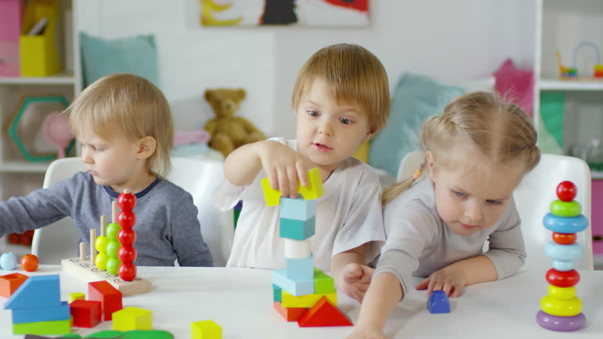 Funny little boy making toy tower with colorful blocks, getting excited and slapping it while playing with friends at table in kindergarten   Shutterstock HD Video #1024772843