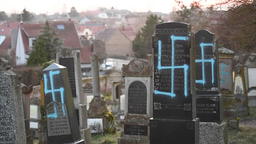 QUATZENHEIM, FRANCE - FEB 20, 2019: Established Shot of vandalized graves with nazi symbols spray-painted on the damaged graves - French Jewish cemetery in Quatzenheim near Strasbourg