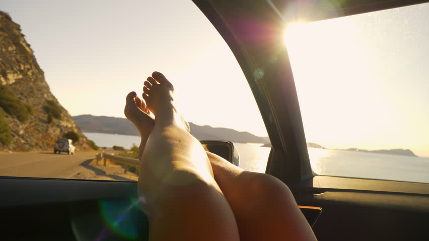 SLOW MOTION, SUN FLARE, POV: Sitting in car with your bare feet out the window while watching the picturesque French seaside. Carefree female tourist stops by the side of the road to rest during trip. #1024777109