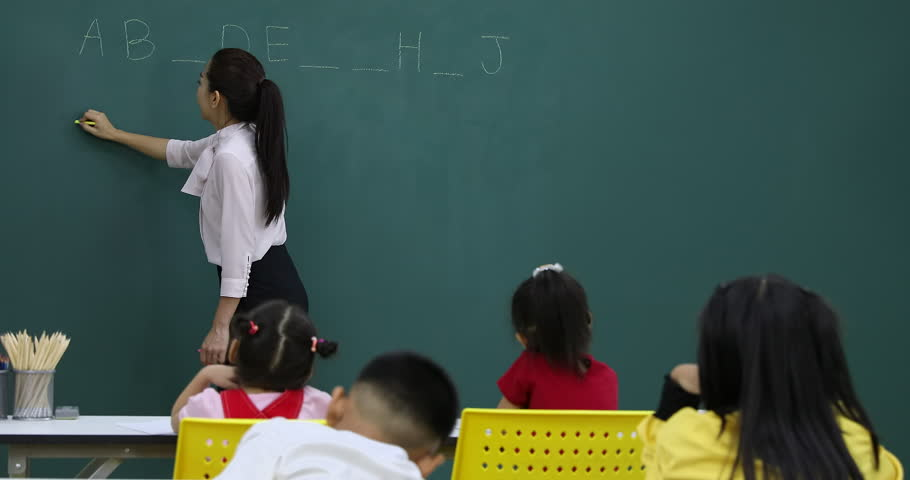 In English class, Asian teacher writes fill in the blanks game on green board, to play with her students