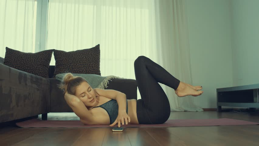 Young woman doing sports at home, Female fitness training in sportswear in the room     Shutterstock HD Video #1024823204