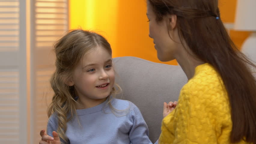 Laughing mom and little cheerful girl cuddling and falling on sofa advertisement   Shutterstock HD Video #1024825226