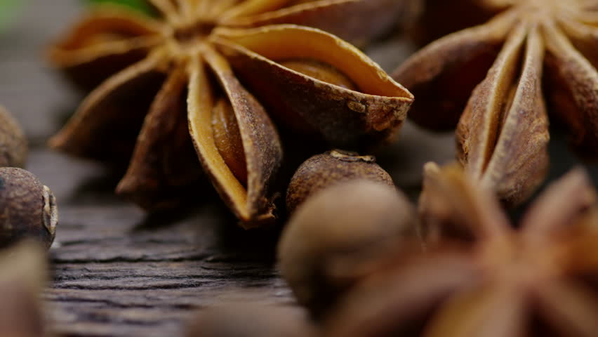 Panning extreme close up of pimento seeds and anise lying on wooden table | Shutterstock HD Video #1024843418
