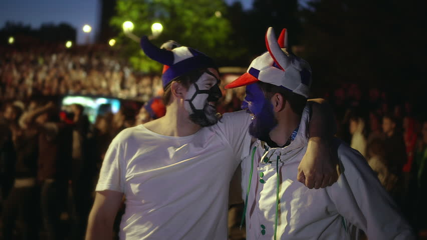 Soccer fan are gay with paint face hugging playfully watching match. People from LGBT community stand stadium amid fan, are smiling each other cutely. Love couple guy embracing watching football match
