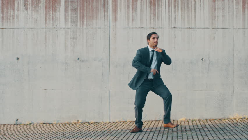 Cheerful and Happy Businessman is Actively Dancing on a Street Next to an Urban Concrete Wall. He's Wearing a Grey Suit. Sunny Day.