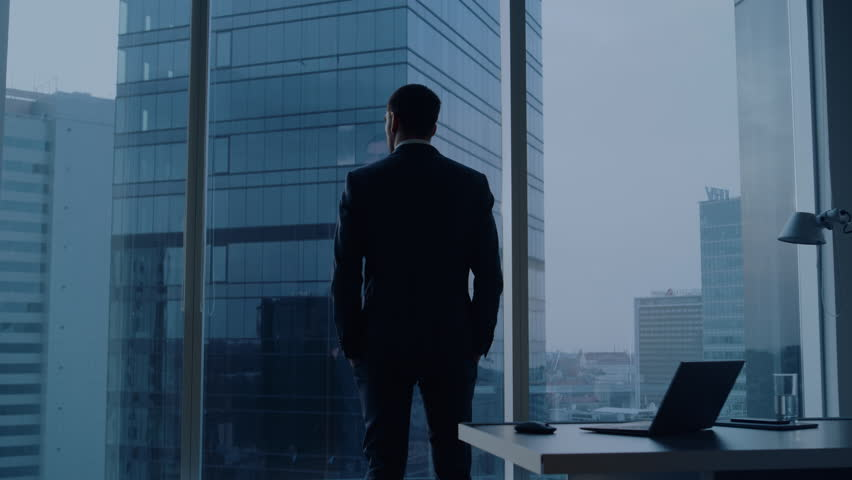 Back View of the Thoughtful Businessman wearing a Suit Standing in His Office, Contemplating Next Big Business Deal, Looking out of the Window. Business District Panoramic Window View | Shutterstock HD Video #1024870199