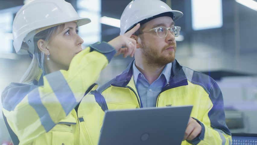 At the Factory: Male Mechanical Engineer Holds Component and Female Chief Engineer Work on Personal Computer, They Discuss Details of the 3D Engine Model Design for Robotic Arm. | Shutterstock HD Video #1024871570