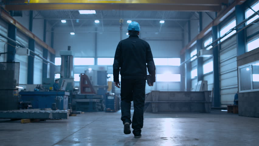 Following Shot of Professional Factory Worker Wearing Hard Hat Holds Tablet Computer, Walking Thorugh Modern Industrial Manufacturing Facility Royalty-Free Stock Footage #1024871918
