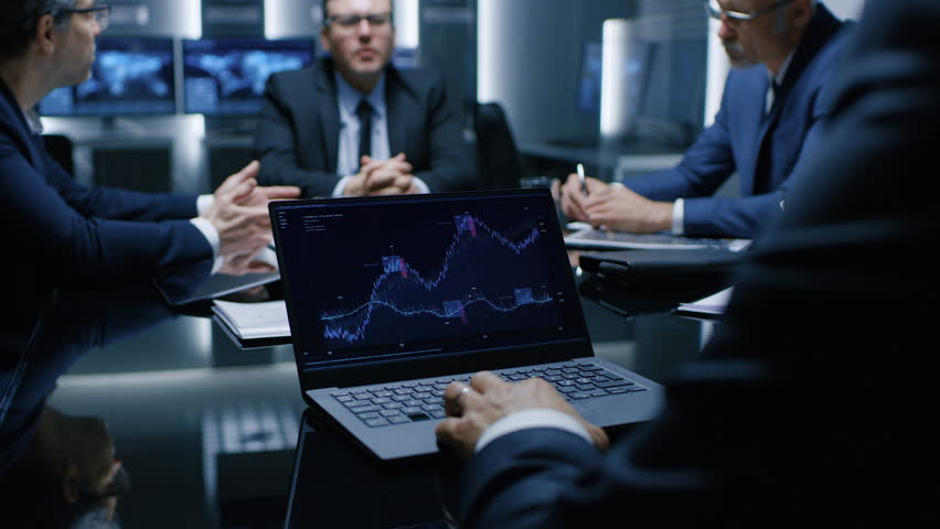 Laptop Standing on the Desk Shows Statistics, Graphs and Charts of Company Growth in the Background Meeting of Businesspeople and Lawyers Sitting at the Negotiations Table in the Conference Room Royalty-Free Stock Footage #1024872668