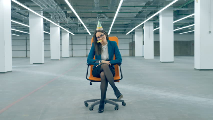 Office worker blows a penny whistle, wearing a birthday cap. Boring birthday concept. | Shutterstock HD Video #1024873859