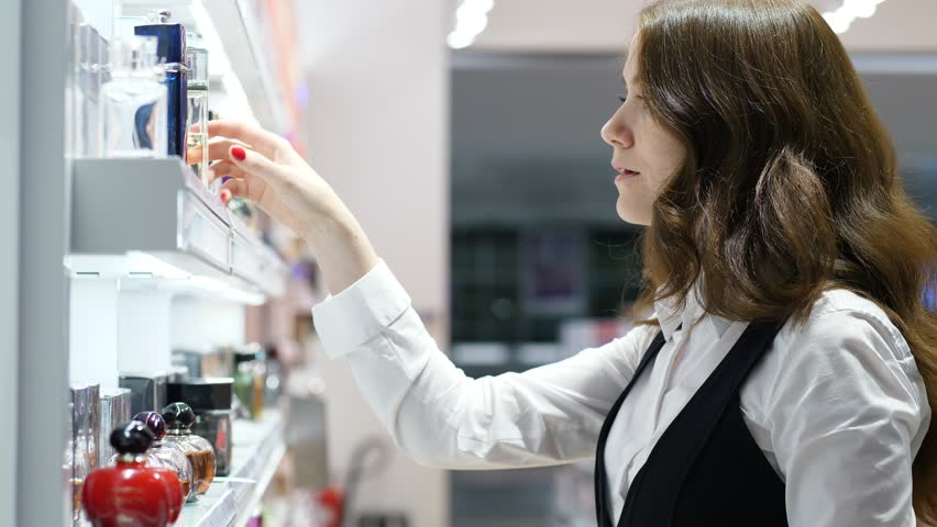 Brunette woman (model released) at airport perfumery shop, take one bottle from shelf, turn in hands and look beside. Close up shot of typical customer in duty free store at terminal sterile area | Shutterstock HD Video #1024883480