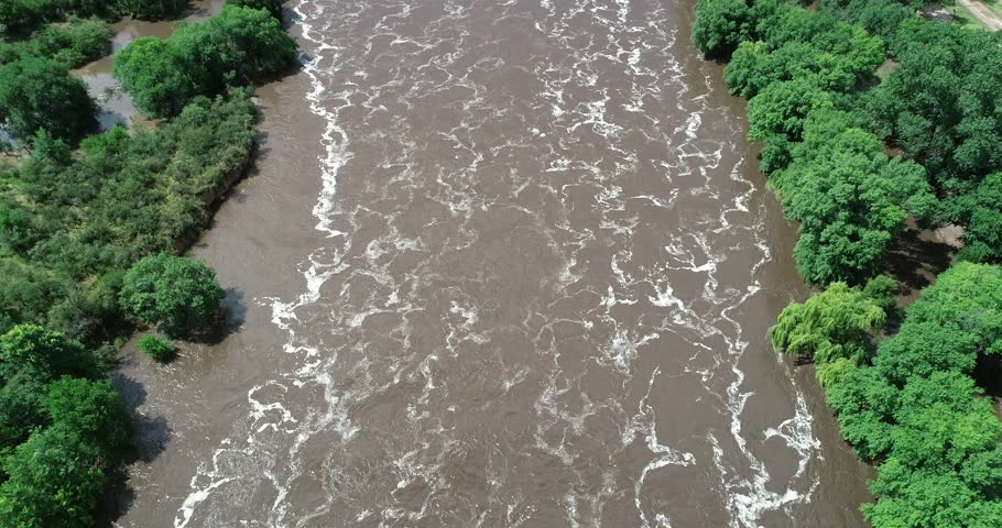Senital aerial drone scene of brown forest turbulent river with foam drawings over surface. Flying fowards over water. Polluted waters. Cordoba, Argentina | Shutterstock HD Video #1024904144