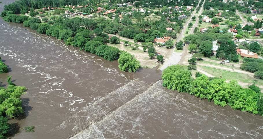 Aerial drone scene of brown strong river passing over bridge. Flood in Mina clavero. Growing river over city streets. Flying backwards discovering flooded town. Cordoba, Argentina   Shutterstock HD Video #1024904159