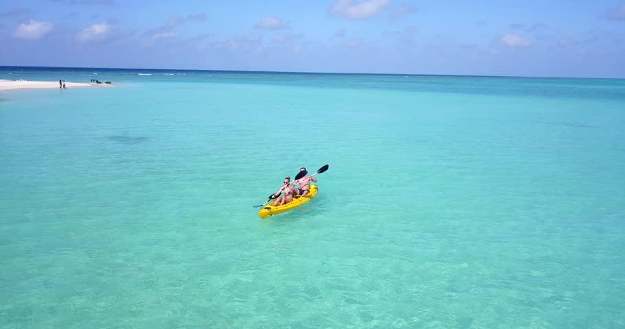 Man and woman couple paddle canoe over beautiful Hawaiian waters on tropical vacation 4k