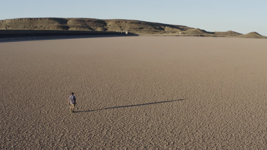 Climate change.  Aerial view of a devastated farmer walking across a dry dam due to drought from climate change and global warming