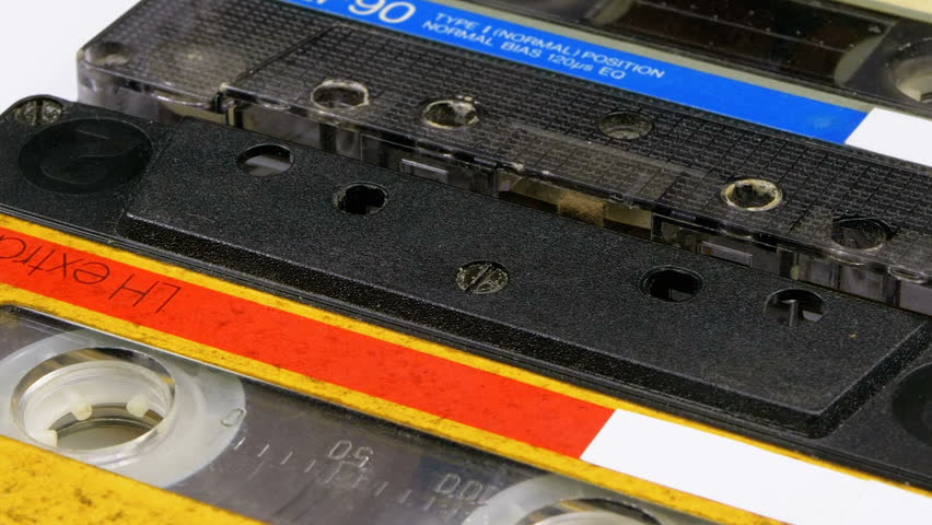 Two Audio Cassettes Rotate on White Background. Yellow and transparent with blue retro vintage tape cassettes with a blank label. Old music. Close-up. | Shutterstock HD Video #1024916981