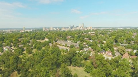 Aerial fly over the residential suburb of Tulsa, Oklahoma with the city skyline on the horizon, on a bright sunny day.