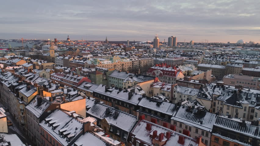 Stockholm city aerial view of buildings in Södermalm. Drone shot flying over snowy rooftops, winter in Stockholm, Sweden