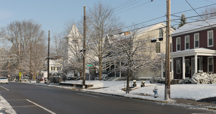 A daytime or morning winter establishing shot of traffic driving in a small town's residential district.  A church steeple in the distance. | Shutterstock HD Video #1024936124