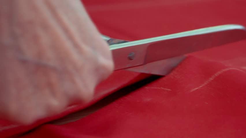 Scissors cut red fabric close-up.