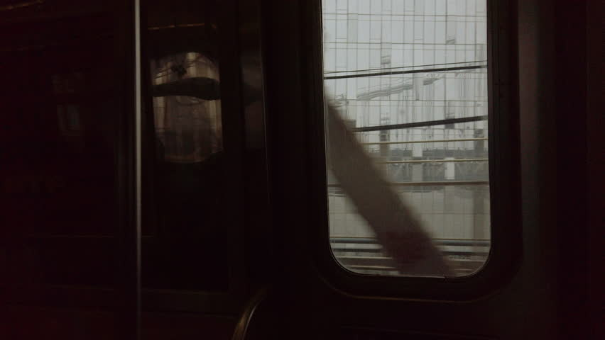Looking out the window of a New York City subway train in motion going over the Manhattan Bridge. Cinematic, hand-held POV shot.