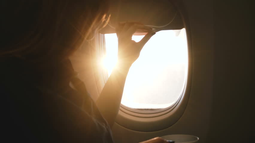 Close-up shot of happy female passenger opening airplane window, enjoying hot drink and amazing sunny view during flight