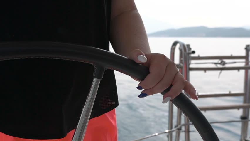Closeup girl steers wheel turning round. Sailing boat with waves splashing   Shutterstock HD Video #1024987946