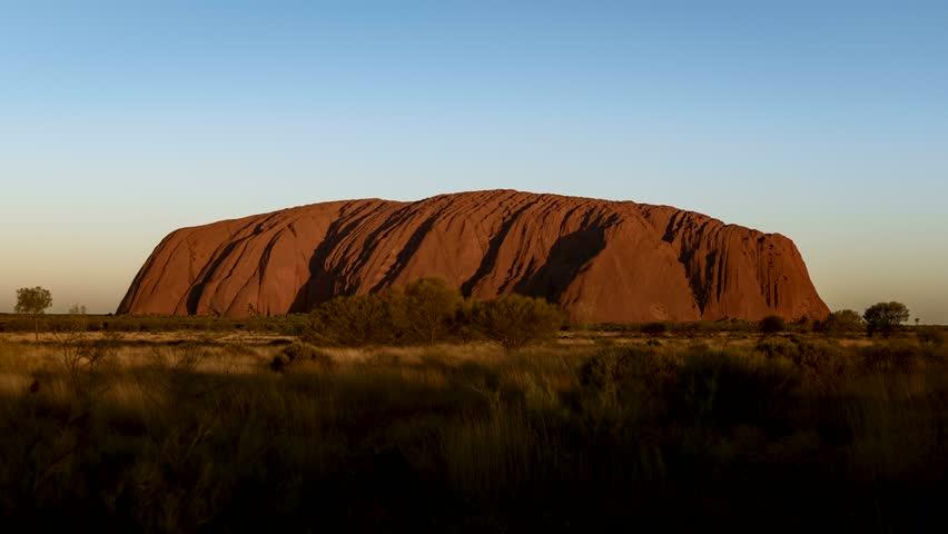 Spectacular time lapse footage of Uluru (Ayers Rock) during sunset. Transition of lights and colors. Australia, Uluru-Kata Tjuta National Park.