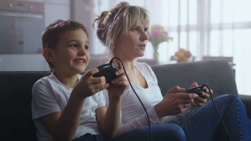 Close up cute preadolescent boy and joyful mother holding joysticks playing video game console sitting on sofa at home. Happy family spending leisure and resting together while playing home console | Shutterstock HD Video #1025030591