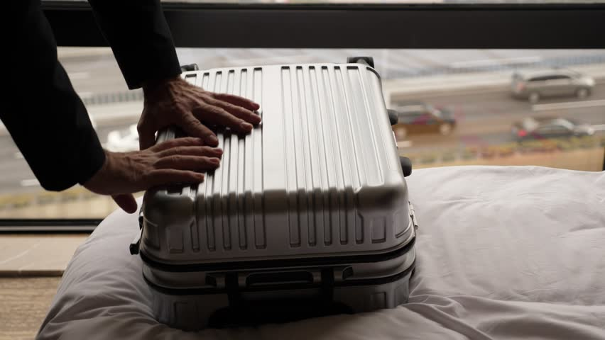 Man put hand on suitcase and push it down to close and lock. Traveller finish packing stuff and ready to leave hotel. Small trolley case lie on bed against window, car traffic seen outside blurred