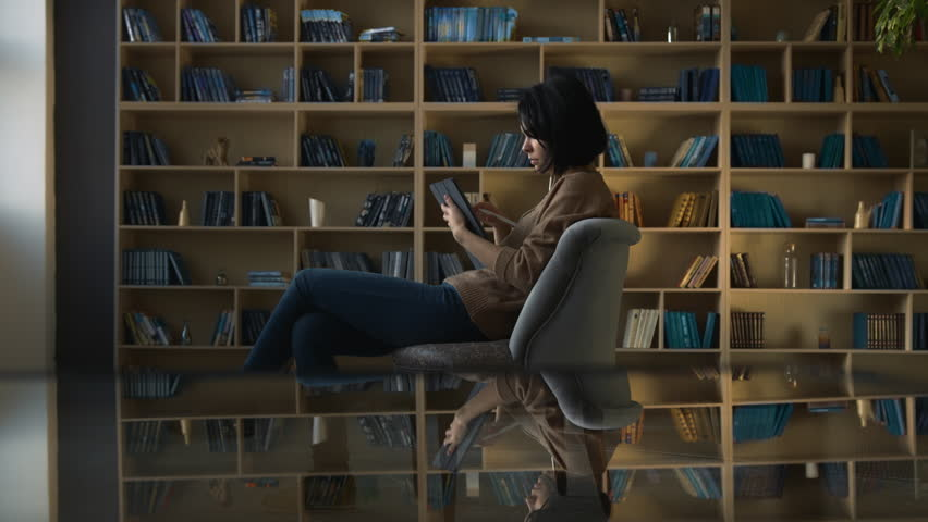 Attractive young woman with tablet PC at home. Pretty girl drawing on digital pad in library. Modern remote education concept. Female student use mobile device with stylus pen for remote study or work | Shutterstock HD Video #1025035127
