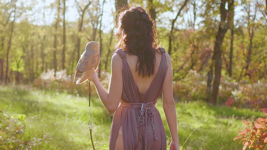 No face, greek goddess with dark curly hair walks in green garden, forest nymph in long brown pussy pale dress, lady with white barn owl on her arm, fairy of spring and animals in bright sunlight