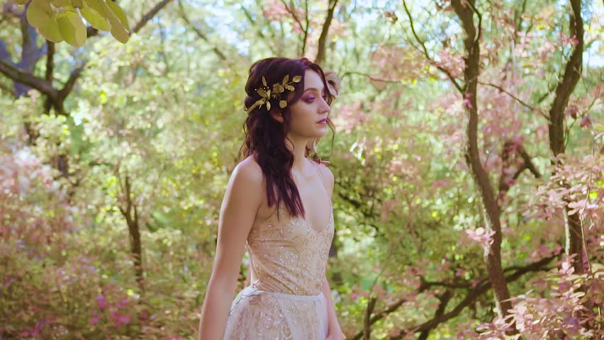 girl with dark curly hair in spring bright green and pink forest in chic expensive beige dress, model shows her long leg in hem section, fairy with golden wreath and barnowl, white owl on shoulder