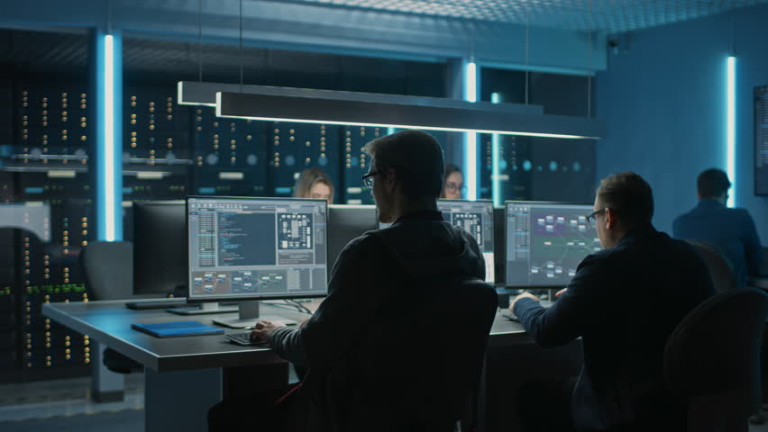 Team of IT Programers Working on Desktop Computers in Data Center System Control Room. Team of Young Professionals Working In Software and Hardware Development, Doing Coding | Shutterstock HD Video #1025052581