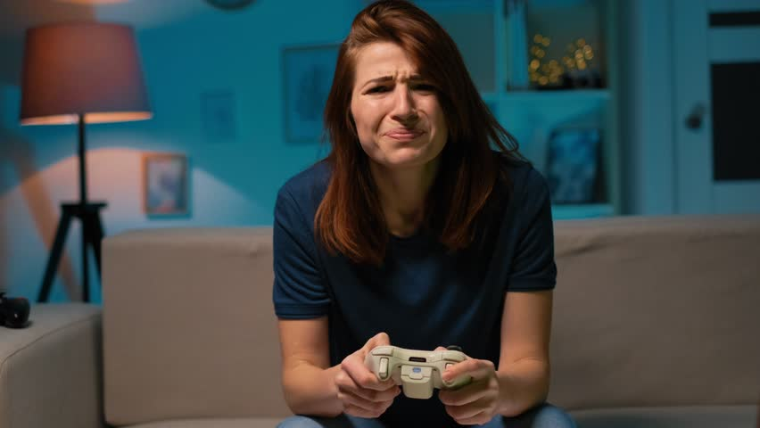 Sad girl loses the video game at home at night. Excited gamer woman sitting on a couch, playing and losing in video games on a console, using a wireless controller. Cozy room, lovely home atmosphere. | Shutterstock HD Video #1025062502