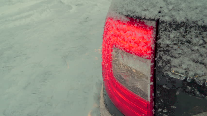 Brushing off the snow on the backlight of the car parked outside the house on a winter season   Shutterstock HD Video #1025067671