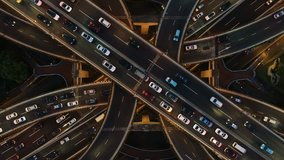 Rising drone shot reveals spectacular elevated highway and convergence of roads, bridges, viaducts in Shanghai at night, transportation and infrastructure development in urban China