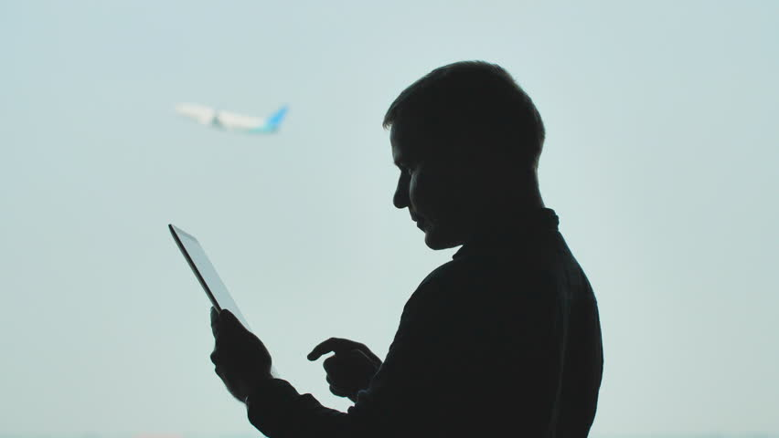 Silhouette of young men using tablet pc on the background of an airplane taking off. | Shutterstock HD Video #1025093948