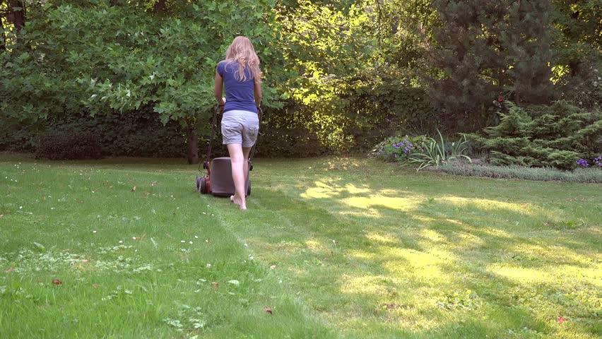 Barefoot blonde woman cut meadow with lawn mower in green garden. 4K UHD video clip. | Shutterstock HD Video #1025105534