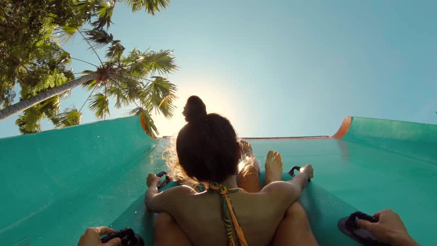 Young Mixed Race Couple Making Selfie Video and Having Fun Sliding Down in a Water Slide. Waterpark Summer Travel Activity Concept. 4K Gopro Footage. Bali, Indonesia.